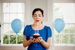 Woman blowing out candles on cupcake
