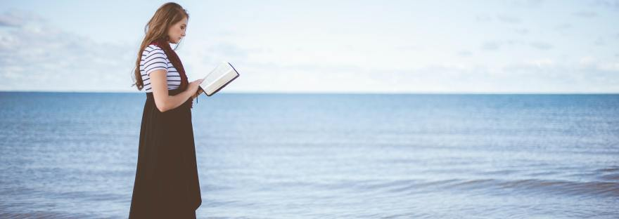 woman with bible by the ocean