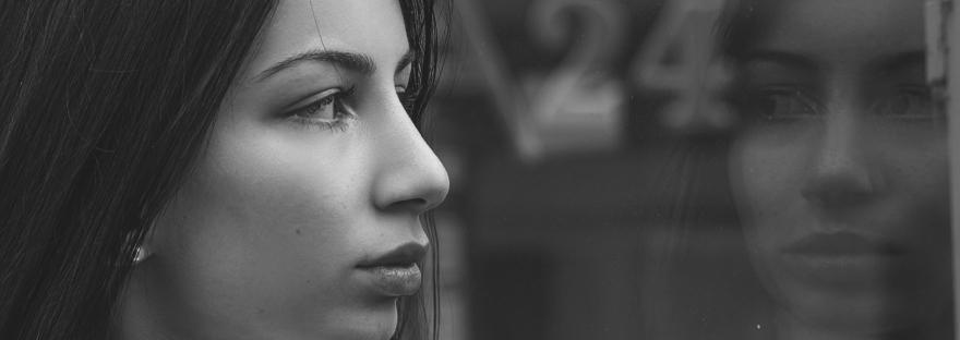 serious woman staring at reflection